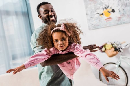 african american dad playing with daughter in living room