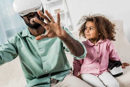 african american man with virtual reality glasses and daughter sitting on sofa