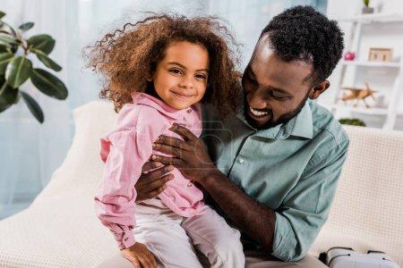Photo pour Fille souriante de père afro-américain tenue sur les genoux dans le salon - image libre de droit