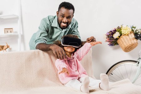 Photo for African american man showing daughter virtual reality glasses in living room - Royalty Free Image