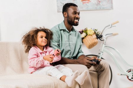Photo for African american father and daughter sitting on sofa and playing video game together in living room - Royalty Free Image
