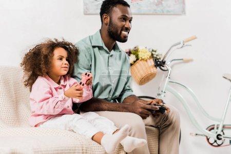 Foto de Americano africano padre e hija jugando videojuegos en la sala de estar - Imagen libre de derechos