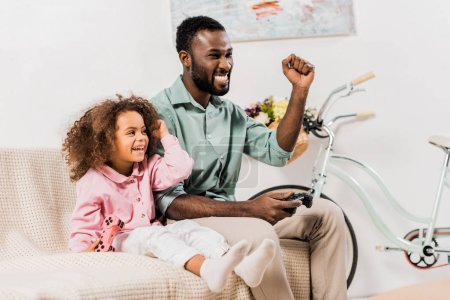 african american dad and daughter playing video game in living room