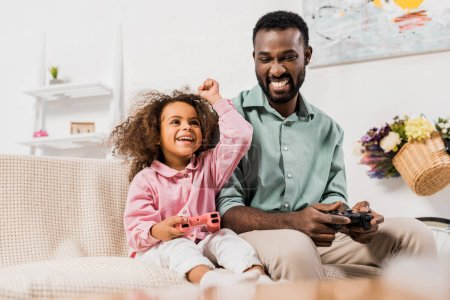 african american father and daughter playing video game with joysticks in living room