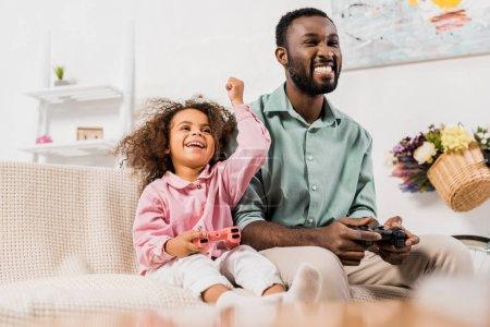 Foto de Papá americano africano riendo con hija y jugando videojuegos en sala de estar - Imagen libre de derechos