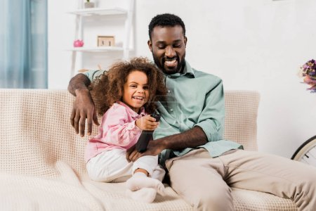 african american dad and daughter watching tv together in living room
