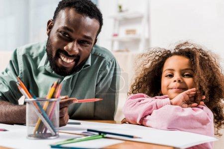 Photo pour Bouchent la vue de père afro-américain crayon et contribuant fille avec le dessin dans le salon - image libre de droit