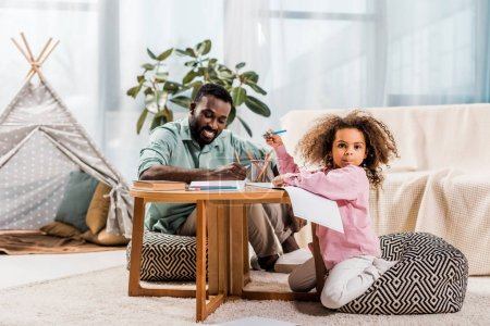 Photo for African american father helping daughter with drawing in living room - Royalty Free Image