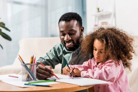 Photo for Close up view of african american father helping daughter with drawing in living room - Royalty Free Image