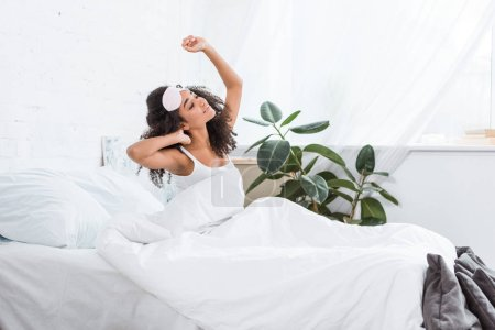 side view of young african american woman with blindfold on forehead stretching in bed during morning time at home