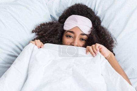 Photo pour Heureuse jeune femme afro-américaine avec bandeau sur le front couvrant le visage de la couverture et la pose dans son lit pendant une heure du matin à la maison - image libre de droit