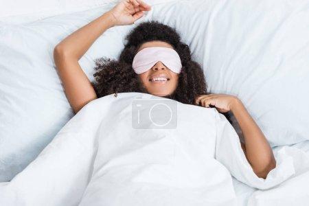 joyeuse fille afro-américaine aux yeux couverts par dormir dans le lit, les yeux bandés pendant le temps de la matinée à la maison