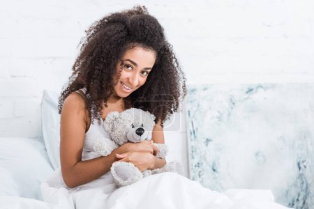 pretty smiling african american curly girl laying in bed with teddy bear at home