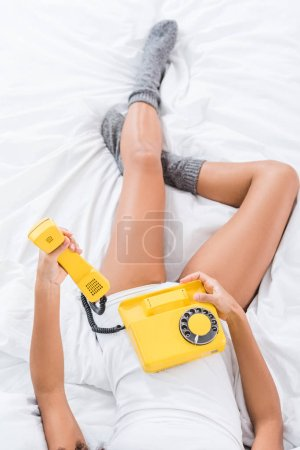 partial view of woman in bed and holding yellow rotary phone