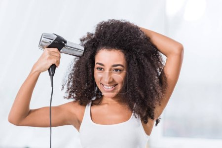 Foto de Sonriendo la chica afroamericana rizado secado el pelo en casa - Imagen libre de derechos