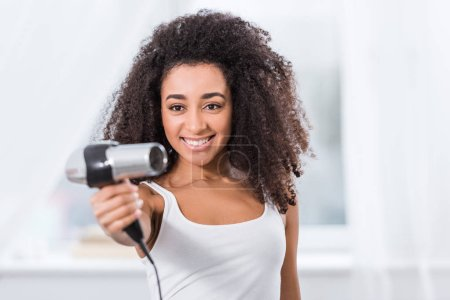 Photo for Joyful beautiful african american girl holding hair dryer at home - Royalty Free Image