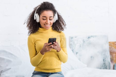 Photo for Attractive young woman in headphones listening music with smartphone at home - Royalty Free Image