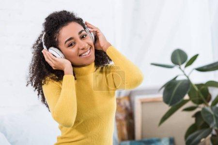 Photo pour Portrait de musique écoute jeune femme afro-américaine dans les écouteurs - image libre de droit