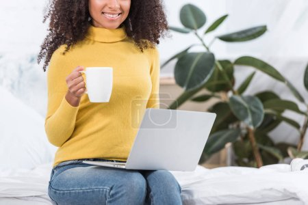 Photo for Partial view of female freelancer with coffee cup working on laptop at home - Royalty Free Image