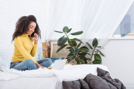 Photo for African american female freelancer talking on smartphone and working on laptop in bed at home - Royalty Free Image