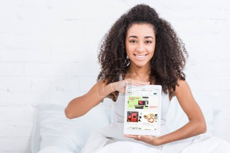 Photo for Happy african american girl showing digital tablet with ebay on screen in bed at home - Royalty Free Image