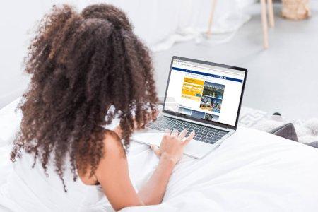 Photo pour Vue arrière de la femme bouclée à l'aide d'un ordinateur portable avec réservation à l'écran au lit à la maison - image libre de droit