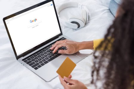 Photo for Cropped image of woman holding credit card and using laptop with google on screen - Royalty Free Image