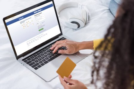 Photo for Cropped image of woman holding credit card and using laptop with facebook on screen - Royalty Free Image