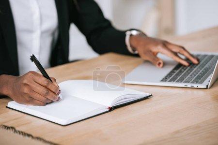 Photo pour Vue cultivée de belle femme américaine africaine écrivant dans le cahier et utilisant l'ordinateur portatif - image libre de droit