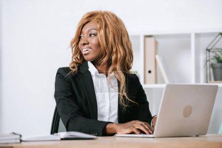 Photo pour Joyeuse femme afro-américaine utilisant l'ordinateur portable au bureau moderne - image libre de droit