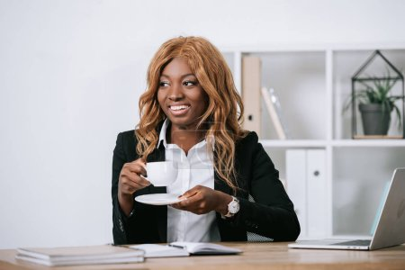 Photo for Smiling african american businesswoman holding cup of coffee in office - Royalty Free Image