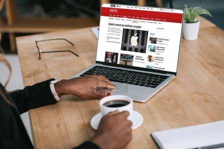 Photo pour Vue recadrée afro-américaine avec ordinateur portable site près de tasse de café - image libre de droit