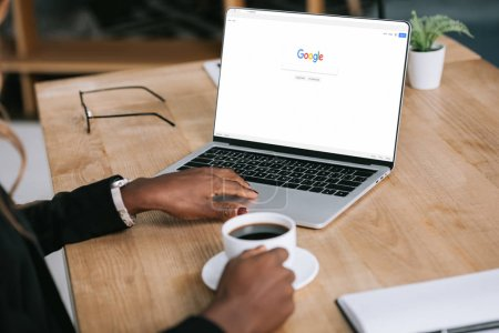 cropped view of african american woman using laptop with google browser near cup of coffee