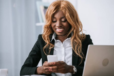 Photo for Beautiful african american businesswoman using smartphone in office - Royalty Free Image