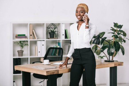 attractive african american businesswoman with short hair talking on smartphone in modern office