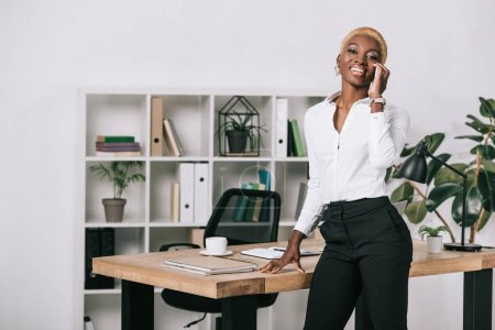 happy african american businesswoman with short hair talking on smartphone in modern office