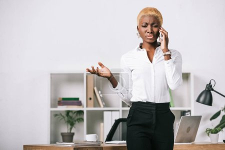 frustrated african american businesswoman with short hair talking on smartphone in modern office