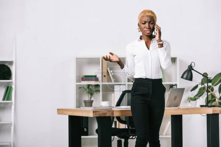 upset african american businesswoman with short hair talking on smartphone in modern office