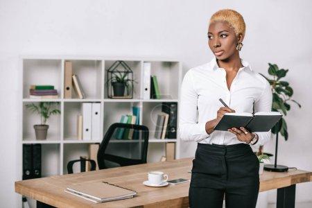 Photo pour Femme d'affaires afro-américains pensif avec les cheveux courts, debout près de table et d'écrire dans cahier - image libre de droit