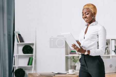 happy african american businesswoman with short hair standing near table with digital tablet