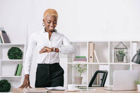 Photo pour Femme d'affaires afro-américains avec des cheveux courts, regardant montre de bureau moderne - image libre de droit