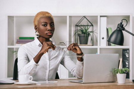confident african american businesswoman with short hair holding glasses in modern office