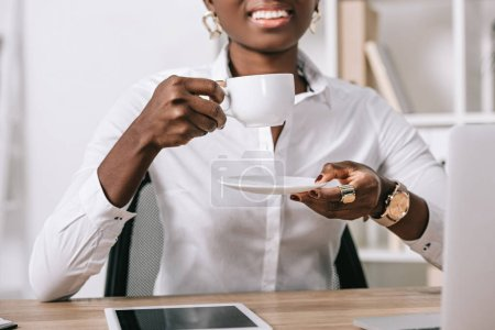Photo for Cropped view of african american woman holding cup of coffee - Royalty Free Image