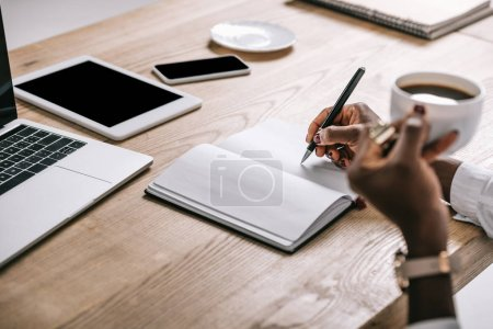 Photo for Cropped view of african american woman writing in notebook - Royalty Free Image