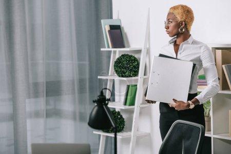 Photo pour Confiante femme afro-américaine tenant des dossiers de bureau moderne - image libre de droit