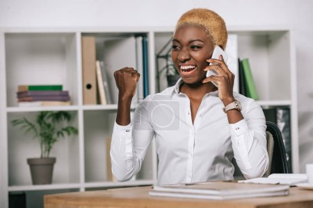 happy african american businesswoman talking on smartphone and showing victory sign