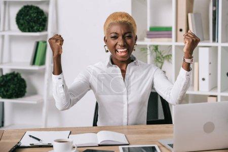 Photo pour Heureuse femme afro-américaine souriante et montrant des signes de victoire - image libre de droit
