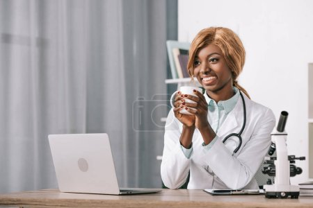 Photo for Beautiful african american scientist holding cup with drink - Royalty Free Image