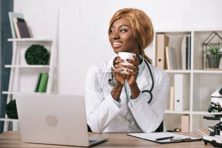 Photo for Smiling female african american scientist holding cup - Royalty Free Image
