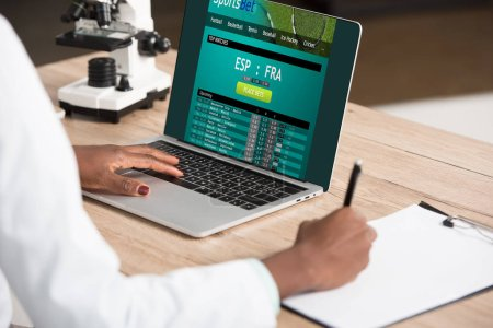 cropped view of african american doctor using laptop with sports bet website near microscope